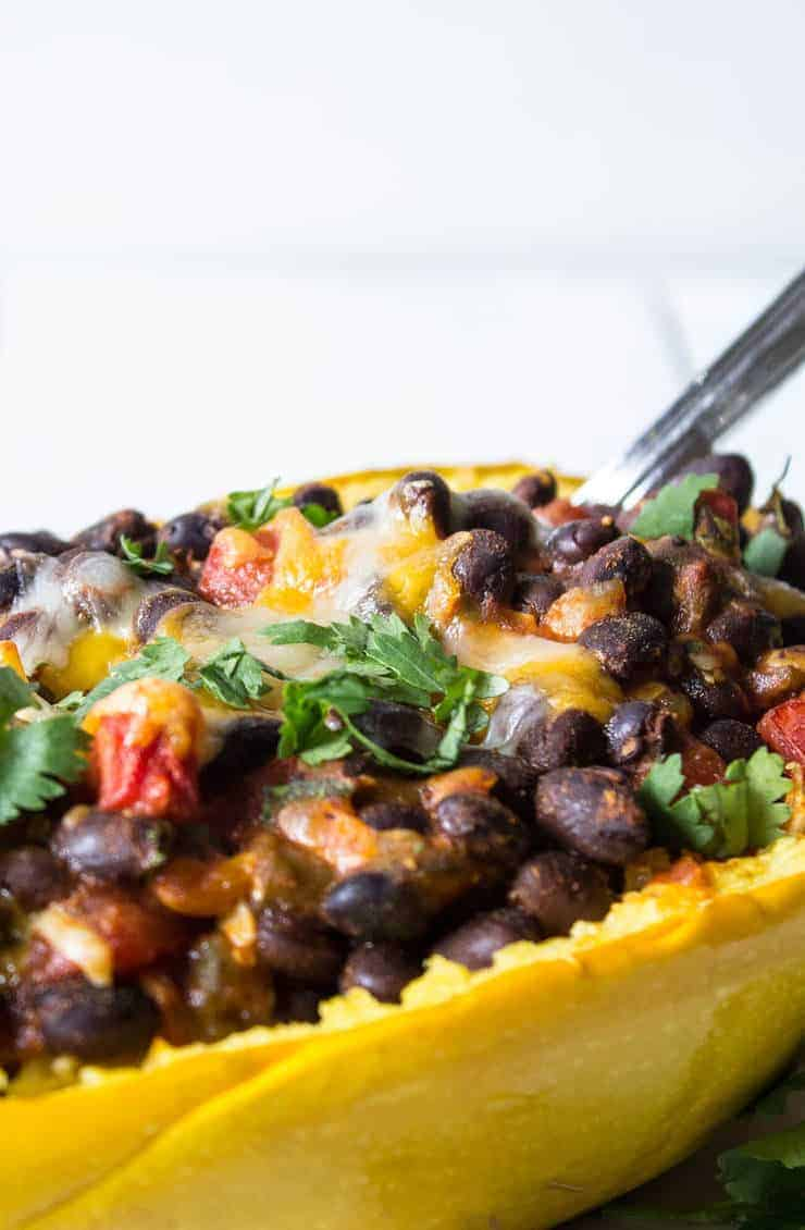 Black beans in a squash shell topped with fresh cilantrol.