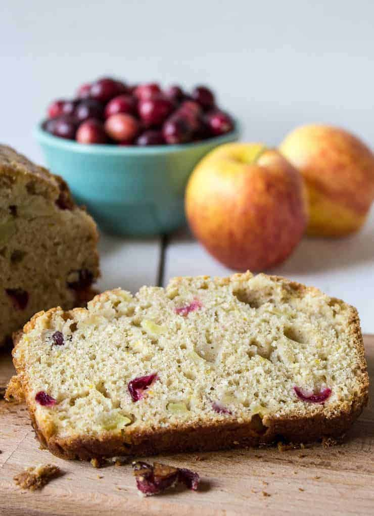 A slice of bread studded with cranberries and apple chunks on a wooden board.