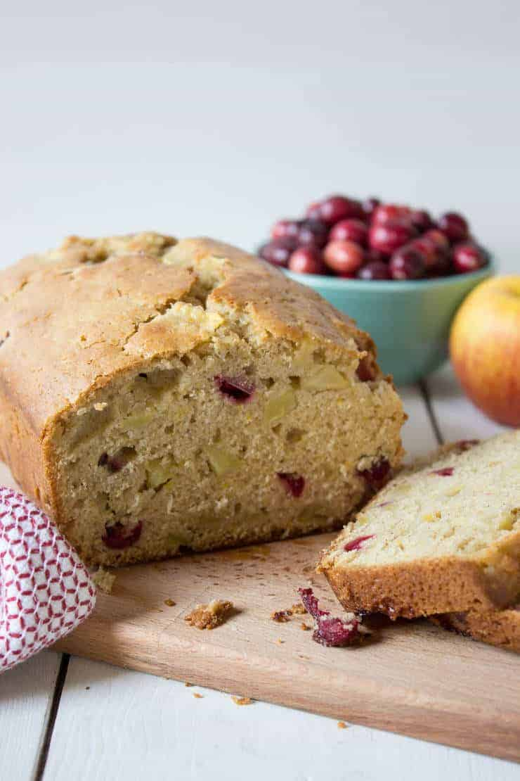 A loaf of bread filled with cranberries and apples on a wooden cutting board.