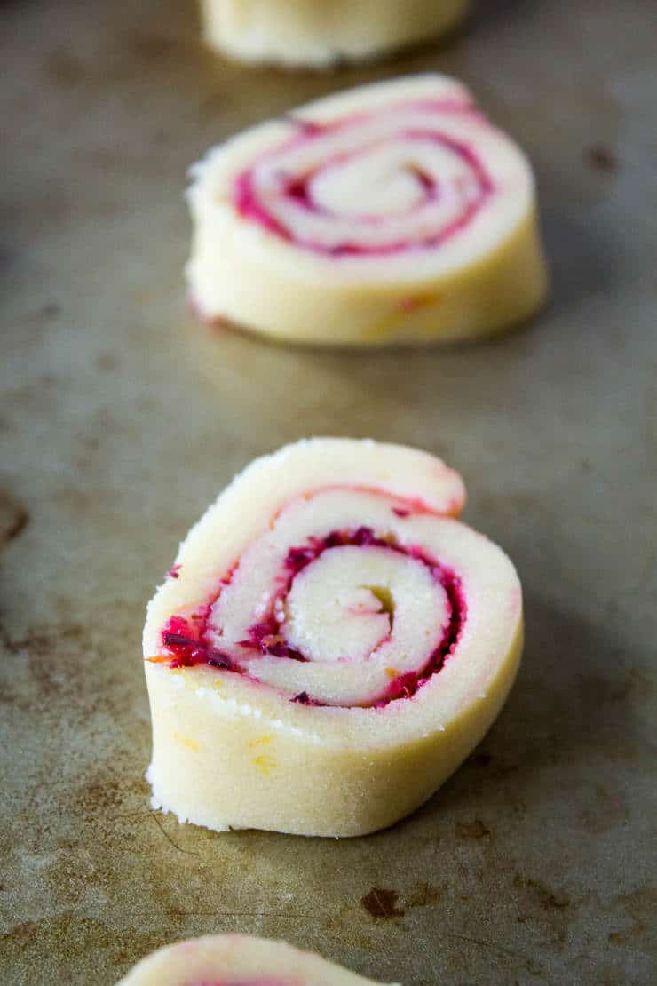 Rolled cookie dough filled with cranberries on a baking sheet.