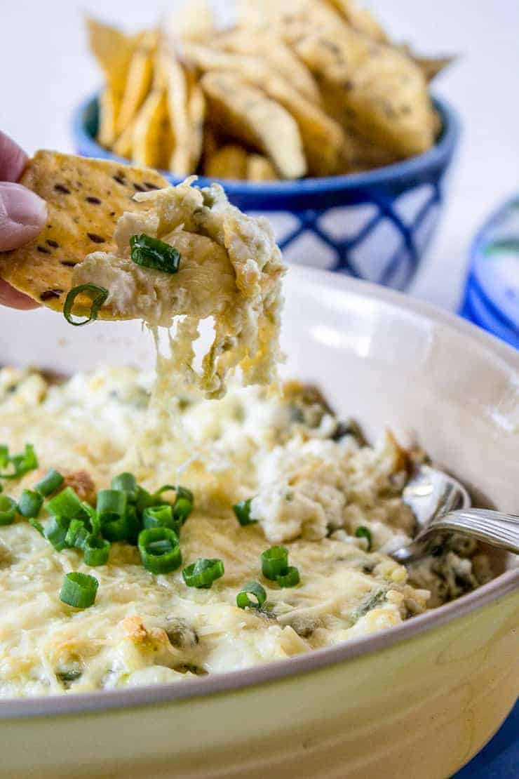 A tortilla chip scooping up cheesy jalapeno popper dip.