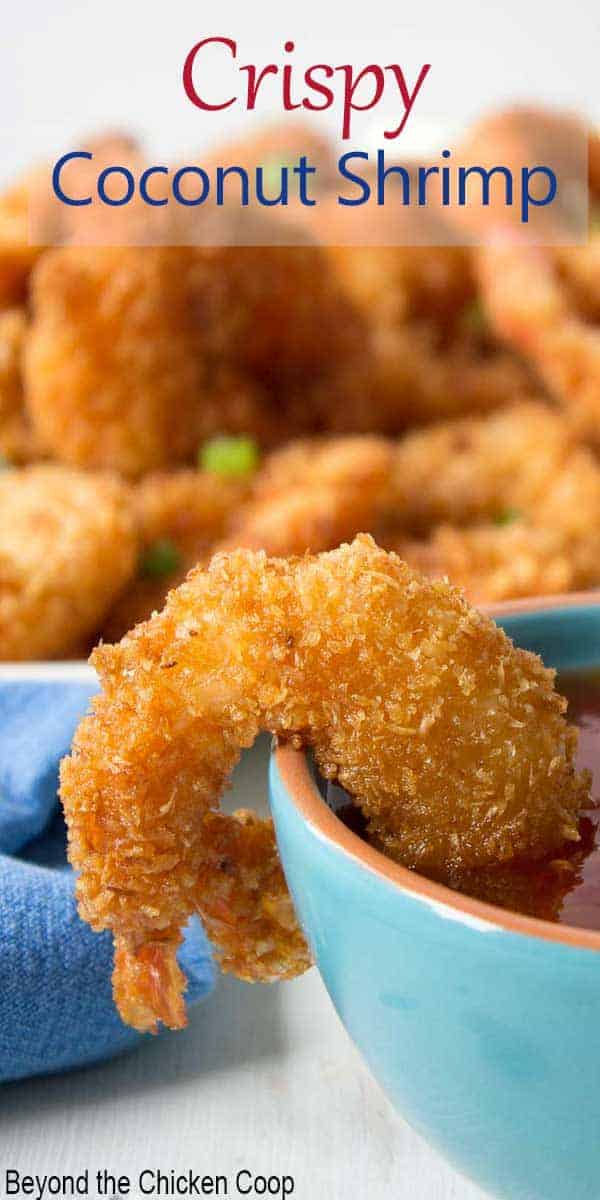 A cooked shrimp with a crunchy coating resting on the rim of a small blue bowl.