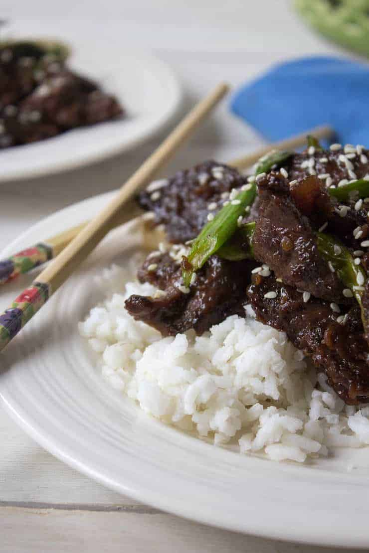 Mongolian Beef served over a bed of rice and topped with sesame seeds.