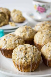 Muffins filled with poppy seeds and topped with a thin icing over the top of the muffins.