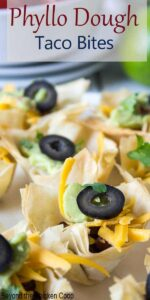 Phyllo dough formed into small cups filled with guacamole, cheese and a sliced black olive.