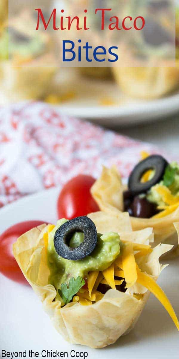 A mini taco cup topped with a sliced black olive.