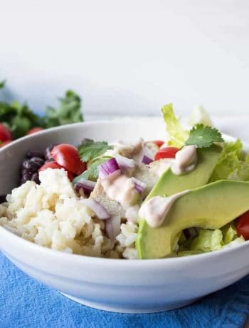 A white bowl with rice, tomatoes, chicken, red onions and avocado slices.