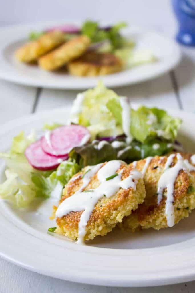 Couscous Cheddar Cakes topped with a dressing on a white plate with a salad.