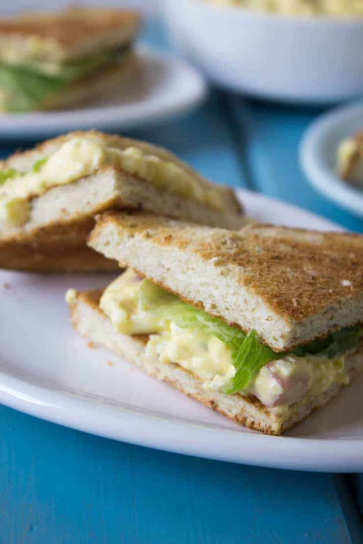 Small sandwiches filled with egg salad and lettuce.
