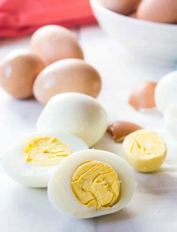 Hard boiled eggs on a white surface with some cut in half and others left whole.