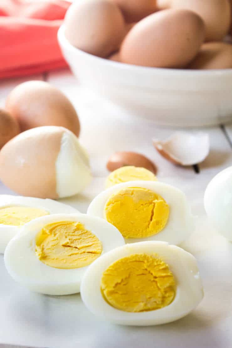 Hard boiled eggs sliced in half with more whole eggs in the background.