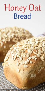 Two loaves of homemade bread topped with oats.