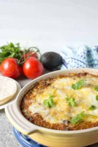 Casserole dish filled with black beans, quinoa and topped with melted cheese.melted