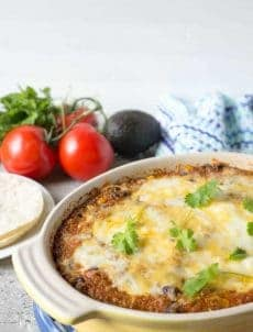 Quinoa Enchilada Bake served in a casserole dish topped with cheese.