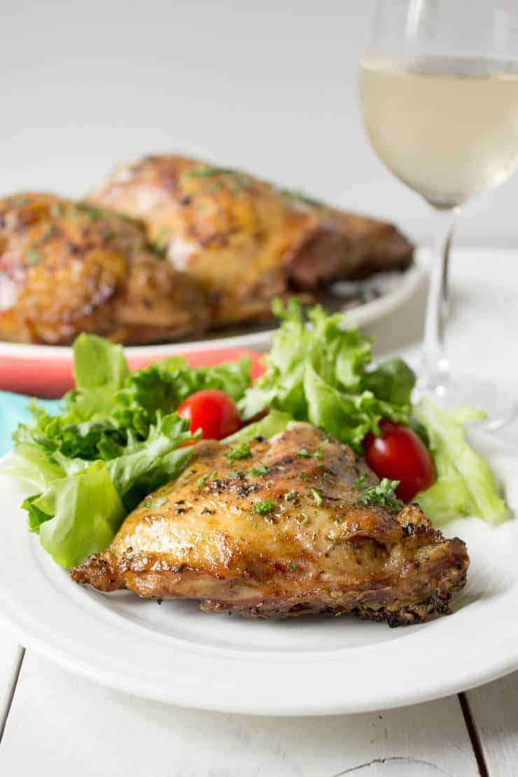 Chicken served on a white plate with a green salad.