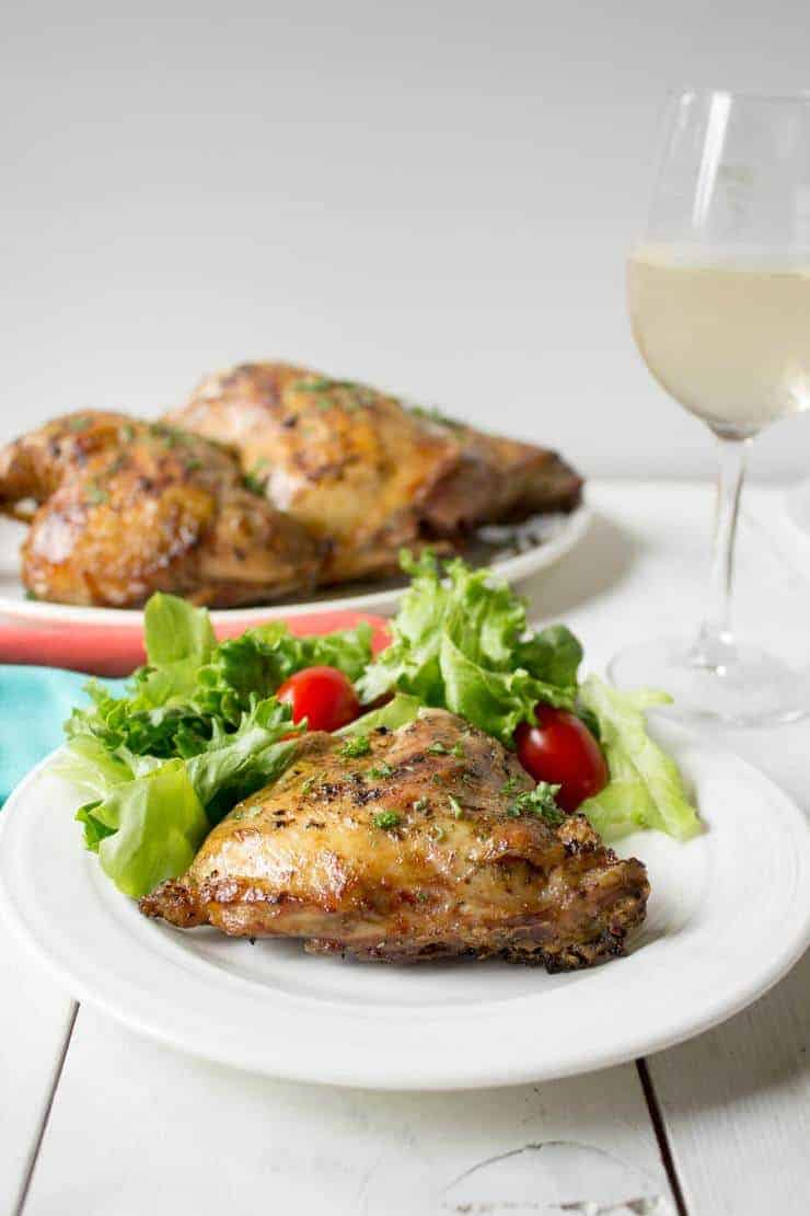 A dinner table set with grilled chicken and a green salad.