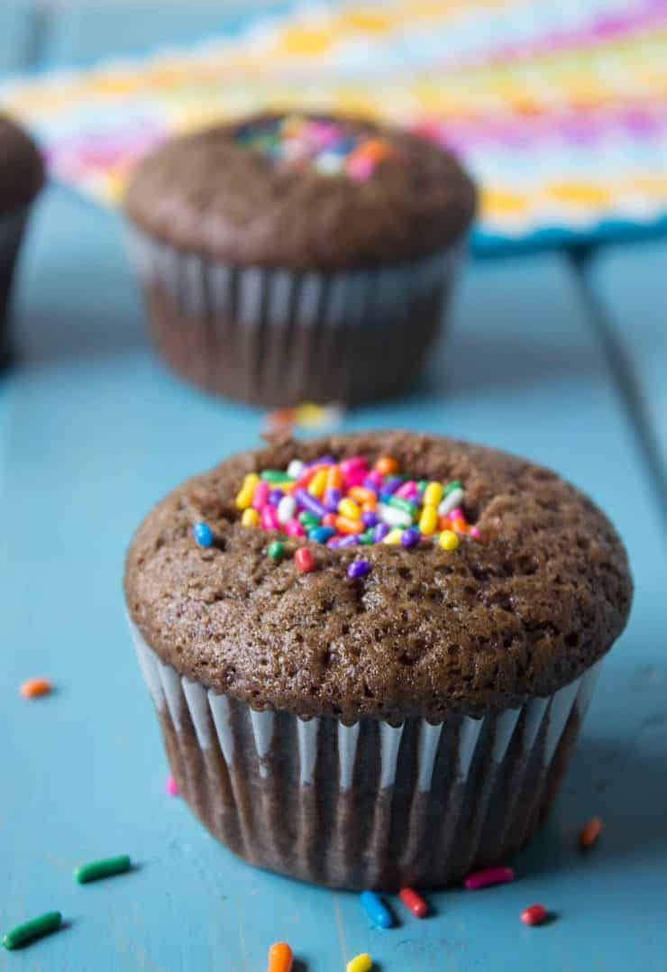 A chocolate cupcake filled with colored sprinkles.