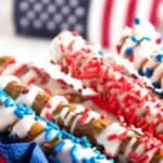 Red and blue sprinkles on pretzels rods covered with white chocolate.
