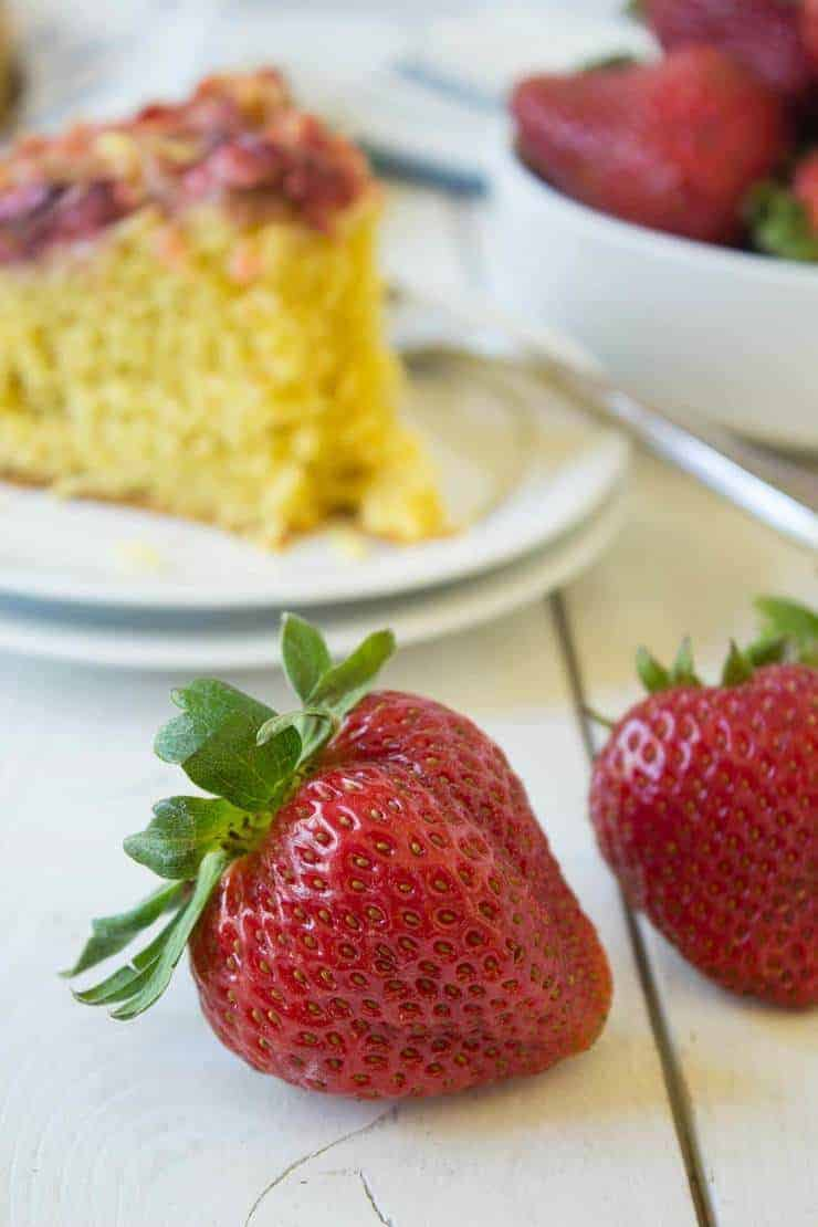 Two fresh strawberries in front of a slice of cake.