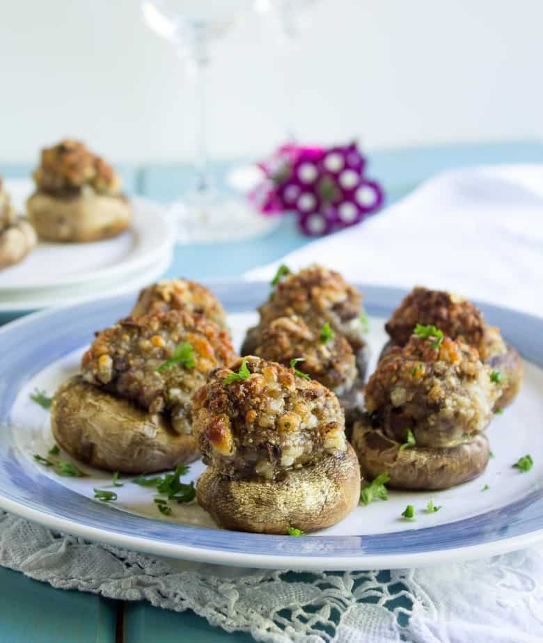 A blue and white plate filled with mushrooms stuffed with sausage.