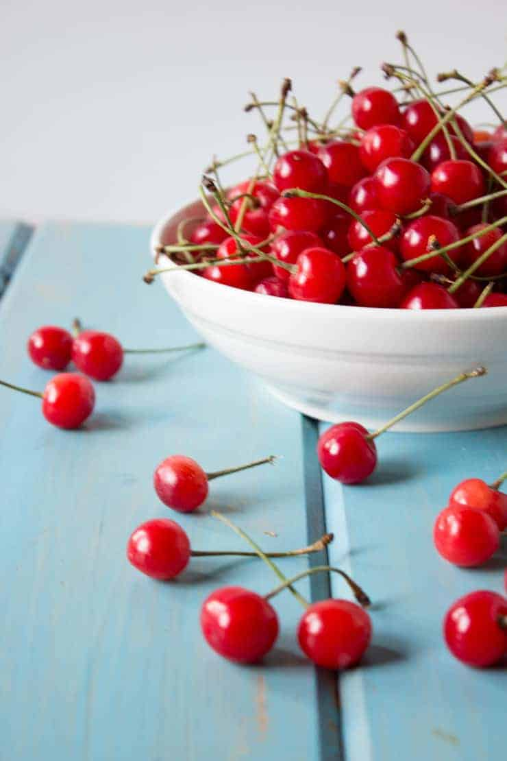 Fresh picked cherries in a white bowl and on a blue board.