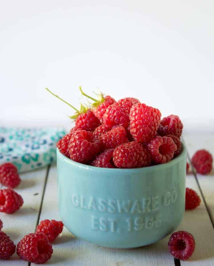 A bowl of fresh raspberries with raspberries in and around the bowl.