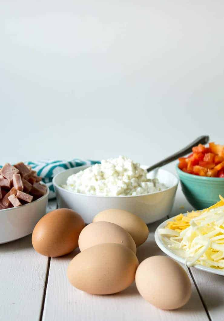 Eggs, cheese, ham and other ingredients on a white board.