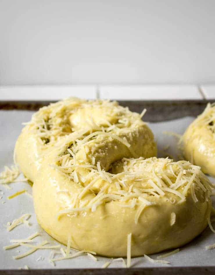 Loaves of bread dough topped with Parmesan cheese.
