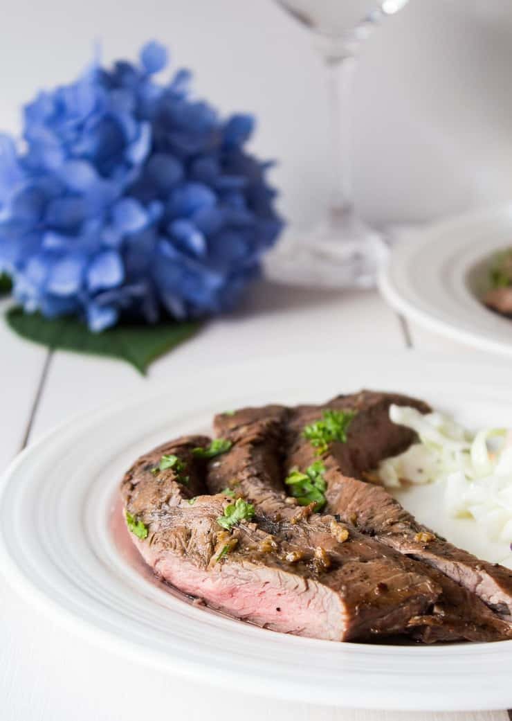 A plate with sliced steak topped with green parsley.