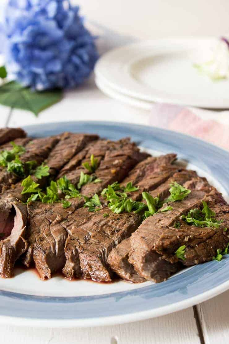 Slice flank steak on a blue and white plate.