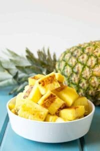 A white bowl filled with chunks of cooked pineapple.