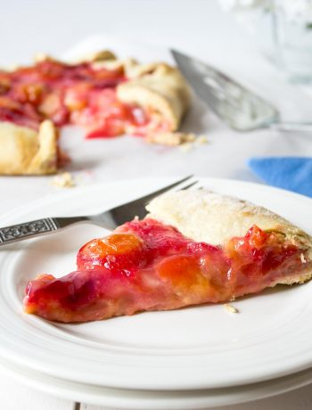 A slice of pie filled with plums resting on a white plate.