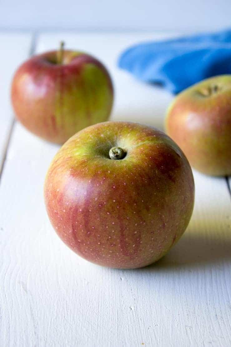 Fresh apples sitting on a white board.