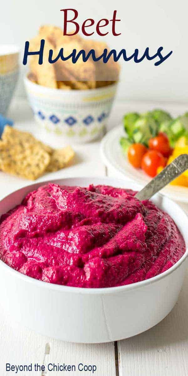 A white bowl filled with pink hummus.