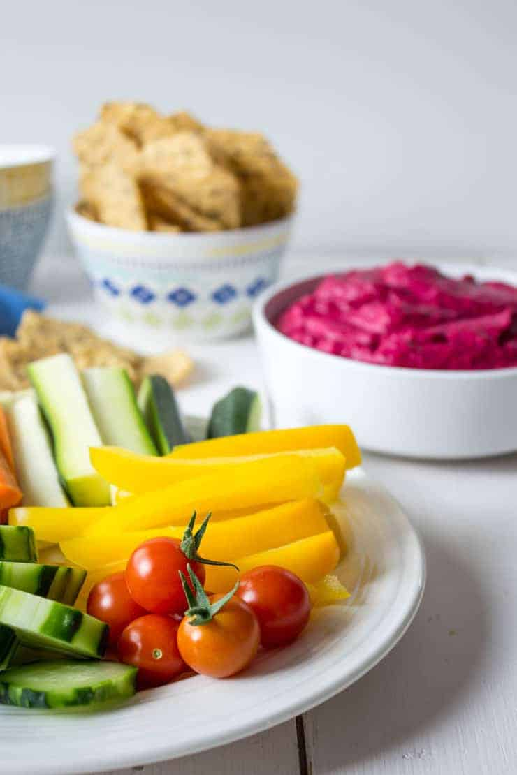 Cut fresh vegetables on a plate and a bowl of bright pink hummus in the background.
