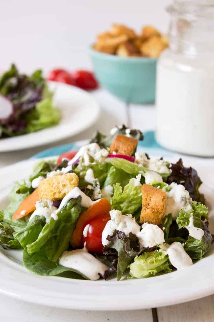 Blue cheese dressing drizzled on a green lettuce salad.