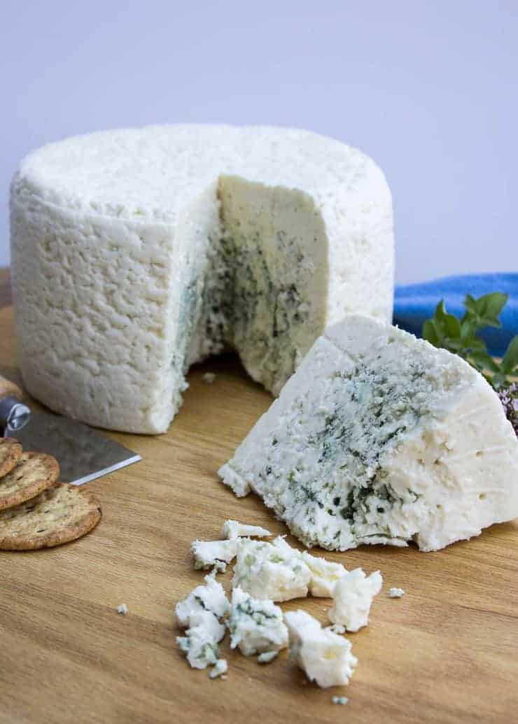 Wheel of blue cheese with a small wedge cut out of the wheel.
