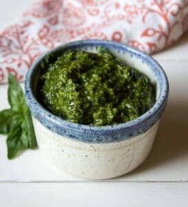 A small bowl filled with a dark green pesto with a basil leaf next to the bowl.