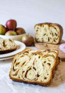 A loaf of apple babka sliced on a board.