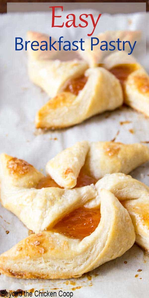 A breakfast pastry filled with apricot jam on a baking sheet.