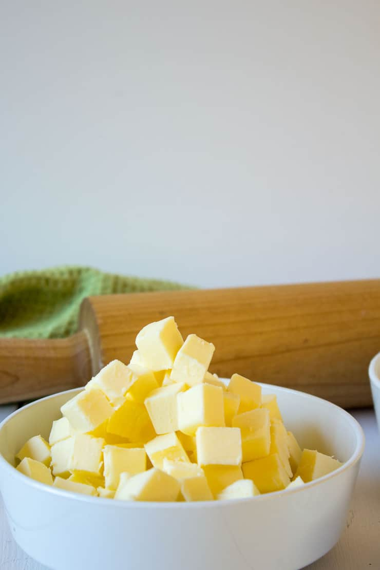 Butter cubed in a small white bowl.