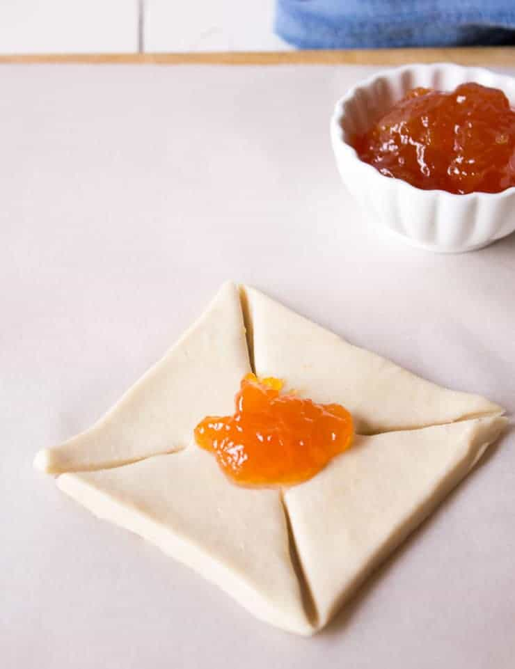 A dollop of apricot jam on a square of unbaked puff pastry.
