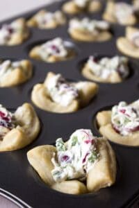 A mini muffin tin filled with puff pastry shells and a cream cheese mixture with cranberries and jalapenos.