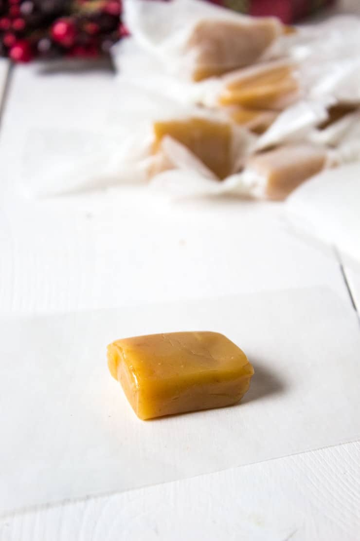 A slice of caramel on a piece of waxed paper.