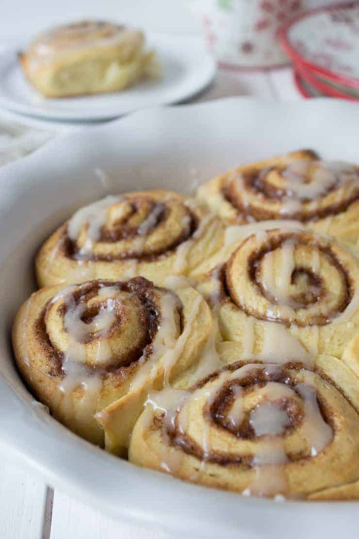 A pan filled with swirled bread topped with a glaze.
