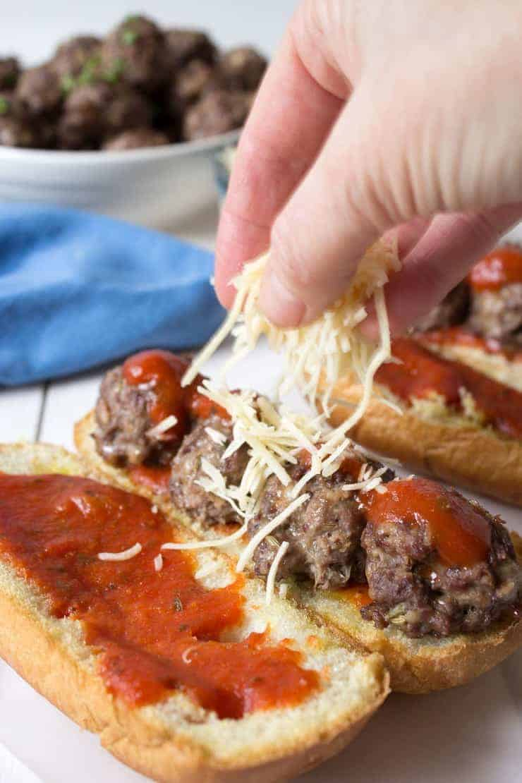 Meatball subs being topped with parmesan cheese.