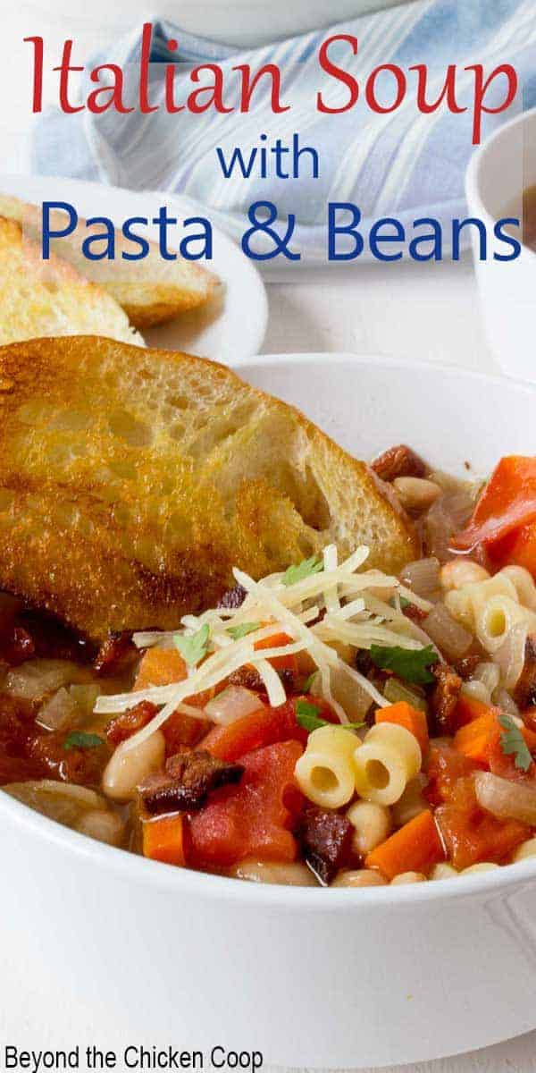 A bowl of soup filled with pasta, beans and vegetables served with a piece of toasted bread.