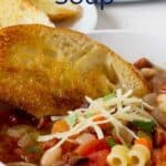 A bowl filled with soup with pasta and beans and a piece of toasted bread on the side.