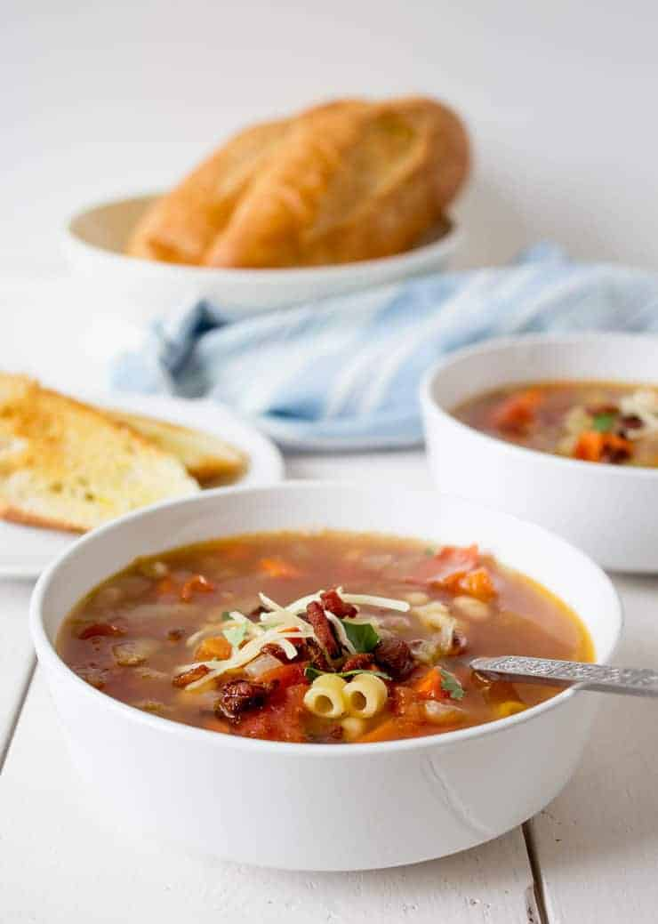 Two white bowls filled with Pasta e Fagioli soup.