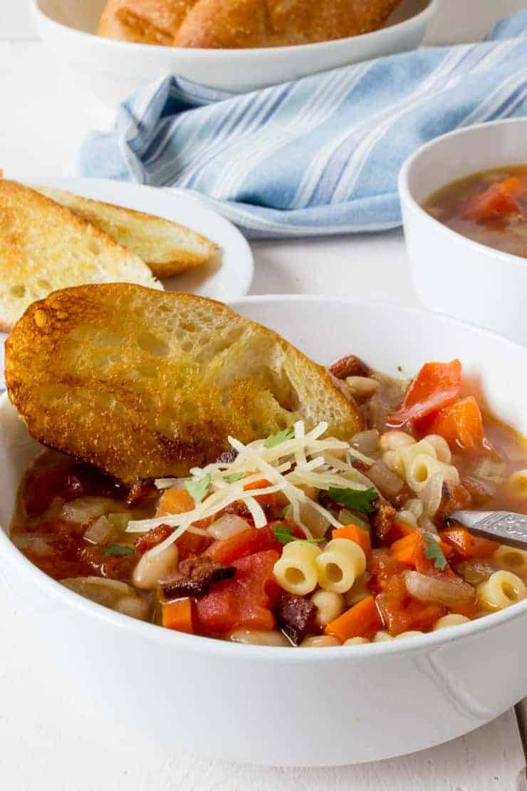 Pasta e Fagioli in a white bowl with crispy toasted bread